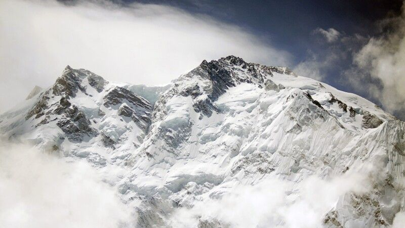 Plötzlich reißen die Wolken auf und der stolze Gipfel des Nanga Parbat kommt zum Vorschein. © Diamir