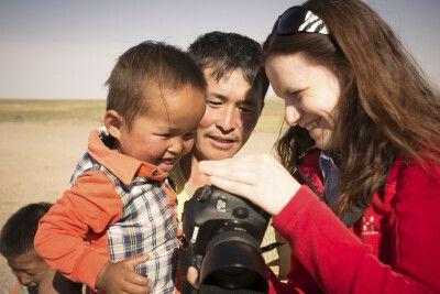 Fotoworkshop-Teilnehmerin zeigt mongolischem Papa und dessen Sohn, das von ihnen geschossenen Portrait.