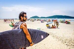 Mit dem Surfbrett am Strand unterwegs
