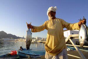 Omani mit Fisch auf dem Fischmarkt