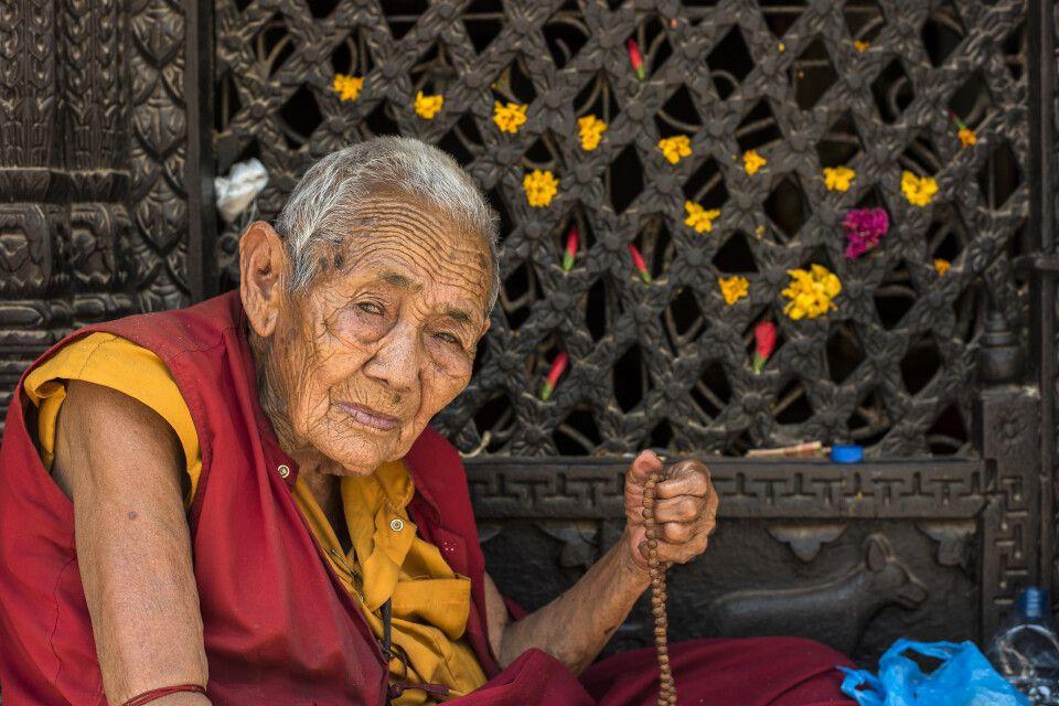 Nonne mit Gebetskette vor einer Gebetsmühle bei der Swayambhunath-Stupa, Kathmandu