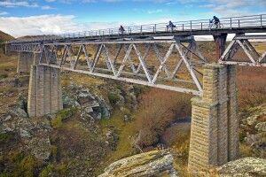 Biker überqueren eine alte Brücke auf dem Otago Rail Trail nahe Oturehua, Central Otago.