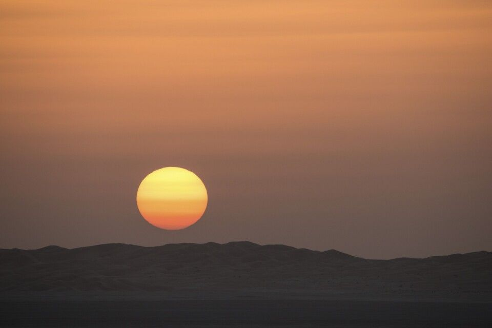 Orangerot verschwindet der Sonnenball hinter den Dünenhängen.