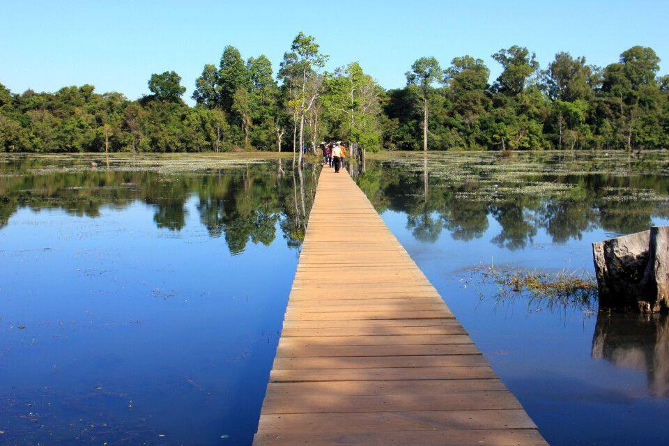 Lange Holzsteg zu einem versteckt liegenen Tempel in Angkor