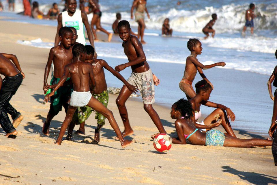 Fussball spielende Kinder am Strand