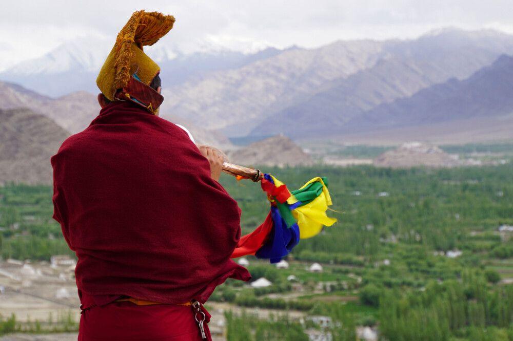 Mönch bläst die Puja auf dem Dach des Klosters von Tikse