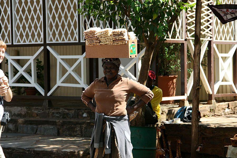 Eine afrikanische Frau mit-Nüssen zum Verkauf