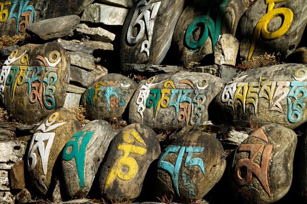 Mani-Steine säumen den Wegesrand, darauf sind buddhistische Gebetsformeln eingemeißelt