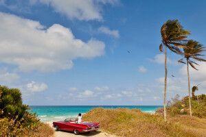 Kubanerin im Oldtimer am Strand