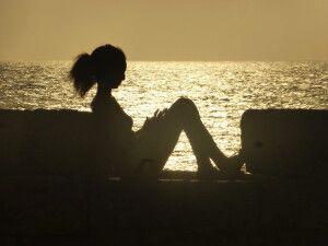Junge Frau genießt den Sonnenuntergang auf der alten Festungsmauer in Cartagena