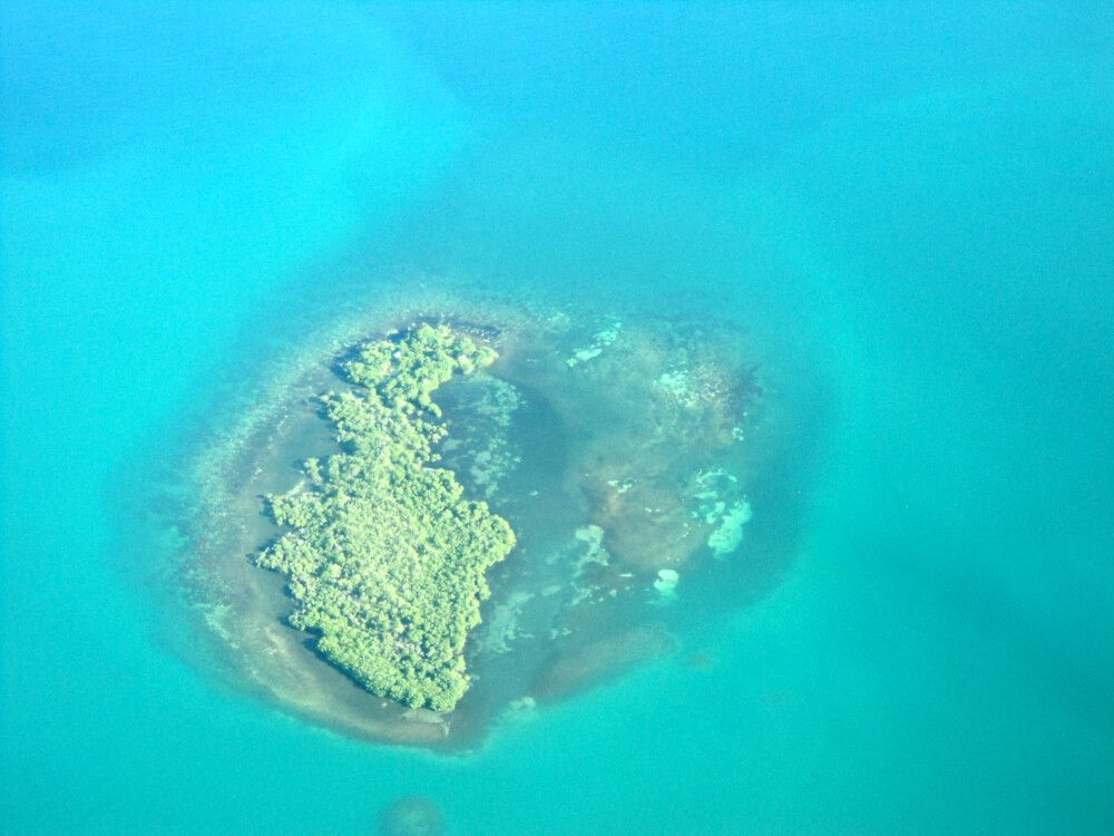 Überflug über eine der zahlreichen vorgelagerten Koralleninseln