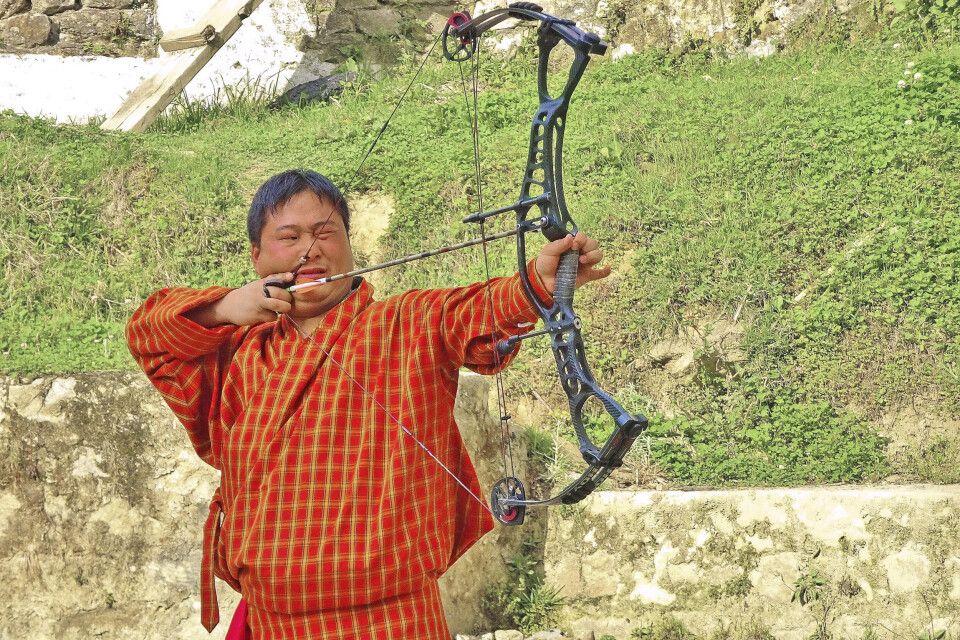 Bhutaner in traditioneller Kleidung beim Bogenschießen