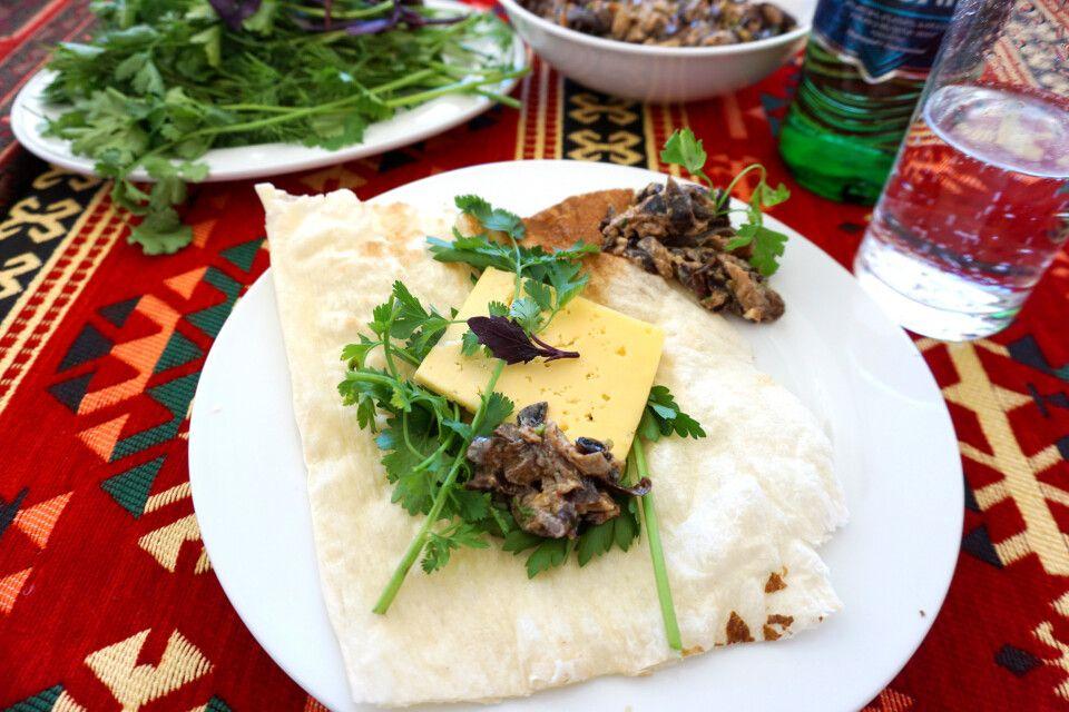 Die Vorspeise zum Mittagessen: frisches Brot, Kräuter, Käse und Pilzsalat