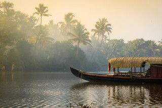 Ein traditionelles Hausboot am Ufer Flusses in Kerala