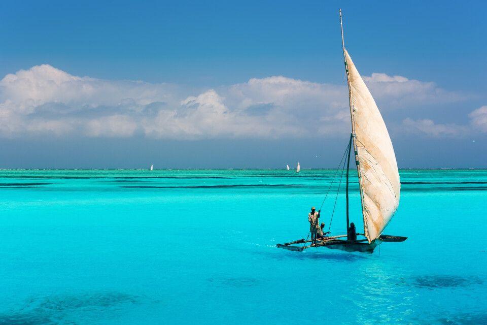 Katamaran auf türkisfarbenem Wasser im Indischen Ozean nahe dem Mnemba Atoll auf Sansibar