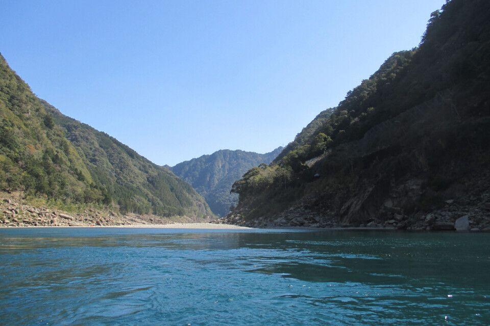 Kristallklares Wasser vor einer traumhaften Bergkulisse erleben Sie bei einer Bootsfahrt auf dem Kumano-Fluss.
