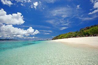 Weißer Sandstrand mit türkisblauem Wasser