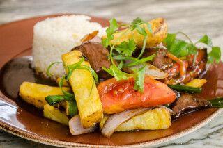 Lomo Saltado ist ein beliebtes Chifa-Gericht (peruanisch-chinesisch), das mariniertes Rinderfilet, Zwiebeln, Tomaten und Pommes Frites kombiniert und mit Reis serviert wird.