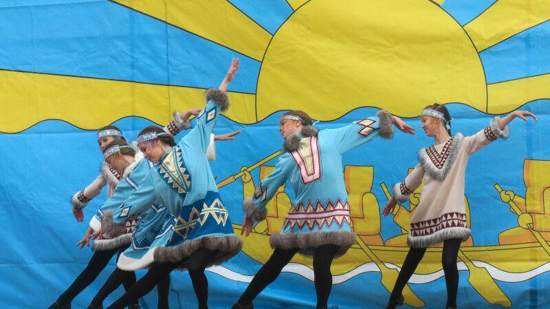 Tanzgruppe in traditionellen Trachten bei nicht ganz so traditionellen Tänzen auf den Beringia-Games © Diamir