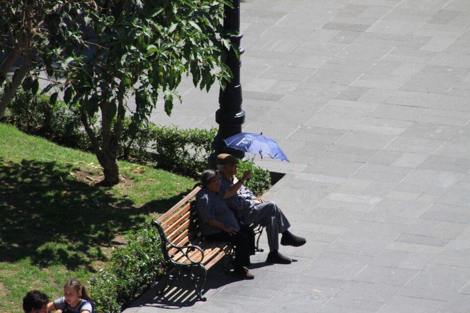 Ein peruanisches Ehepaar genießet den Trubel am Plaza des Armas in Arequipa