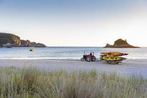 Ein Traktor mit Kajaks am Strand