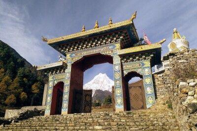 Tor zum Kloster Ribung in Lho - im Hintergrund der mächtige Manaslu