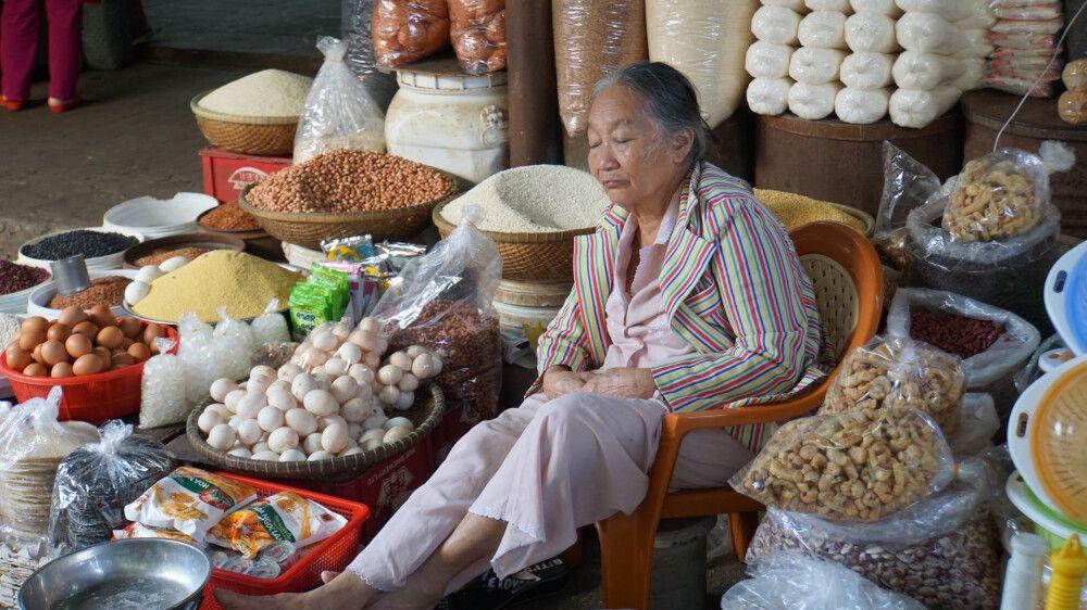 Dösende Verkäuferin auf dem Wochenmarkt in Hue