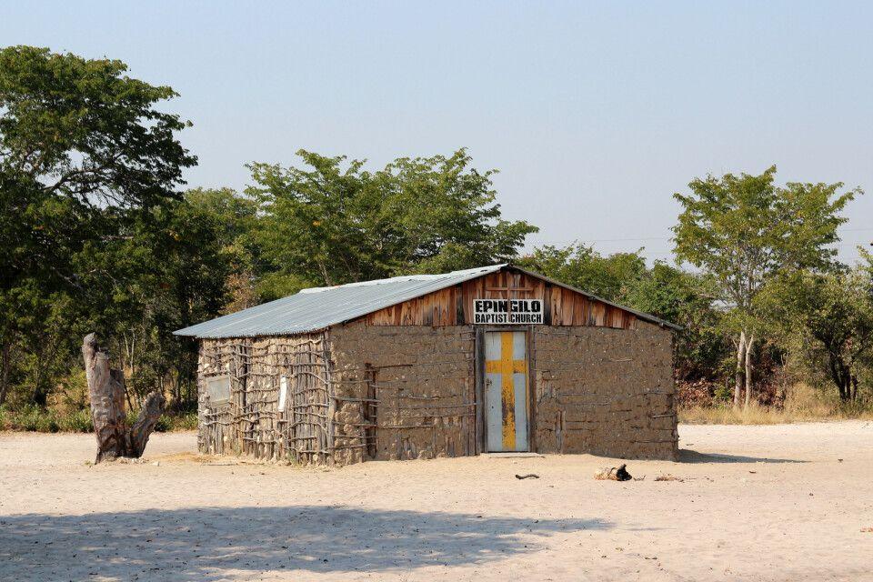 In einem der vielen traditionellen Dörfern im hohen Norden Namibias nehmen wir das Besuchsangebot in dieser kleinen Kirche an.