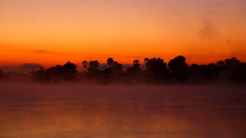 Auch das kann der Sambesi: Nicht rauschend und unbändig, sondern gemächlich und voller Mystik im Abendlicht nach einem pittoresken afrikanischen Sonnenuntergang. © Diamir