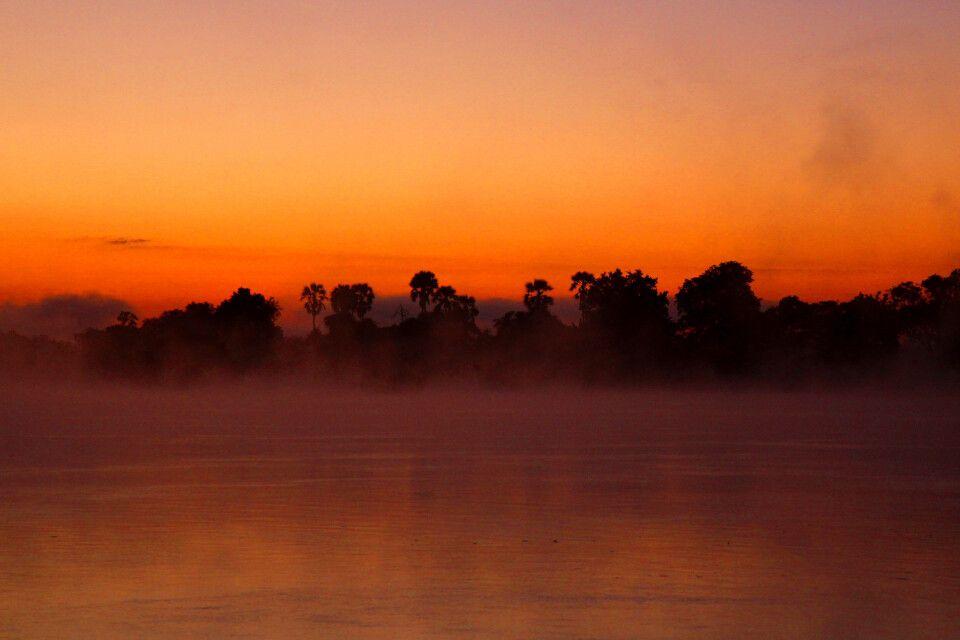 Auch das kann der Sambesi: Nicht rauschend und unbändig, sondern gemächlich und voller Mystik im Abendlicht nach einem pittoresken afrikanischen Sonnenuntergang.