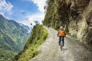 Mountainbiketour in die Yungas bei La Paz. Im Hintergrund kreist ein Kondor über dem Tal.