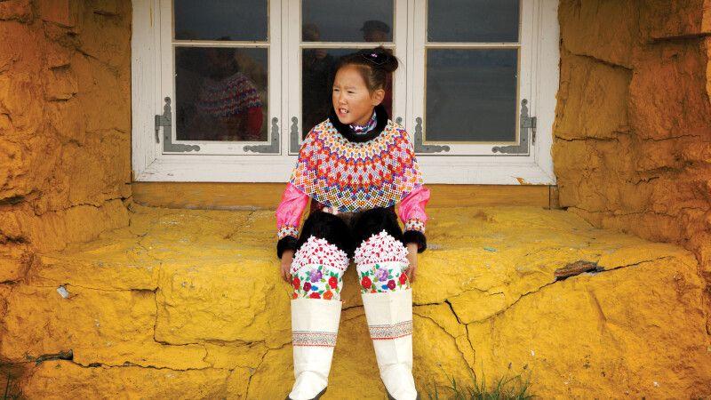 Junge Inuit in traditioneller Kleidung vor einem Haus © Diamir
