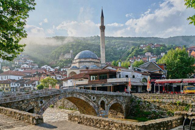 Die alte Steinbrücke überspannt die Bistrica. Im Hintergrund die Sinan-Pascha-Moschee und links auf dem Berg die Festung von Prizren.